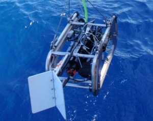 Figure 2. The towed optical assessment device is lowered into the ocean with a 12-V pot hauler and an umbilical cable.