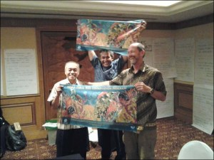 Pak Muhammed Badrudin and Pak Purwanto of the Indonesia Marine and Climate Support Project and Rusty Brainard of the PIFSC Coral Reef Ecosystem Division hold up posters from NOAA's Coral Reef Conservation Program, gifts for all of their hard work as facilitators and translators during the workshop held this March in Jakarta, Indonesia. NOAA photo by Megan Moews