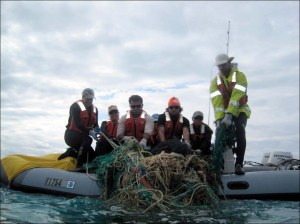 Kerrie Krosky, Kristen Kelly, Edmund Coccagna, Tomoko Acoba, Joao Garriques, Kerry Reardon, and Russell Reardon (from left) of the PIFSC Coral Reef Ecosystem Division on April 8 haul a tangled mass of derelict fishing gear into a 17-ft Avon inflatable boat during a 21-day mission to survey and remove marine debris at Midway Atoll. NOAA photo by James Morioka