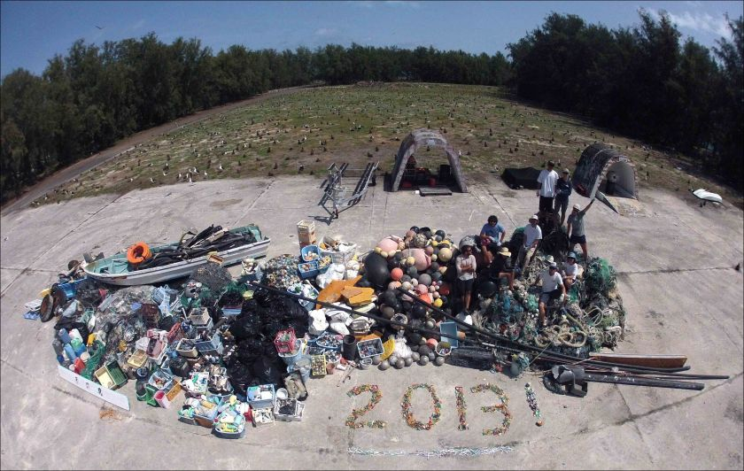 James Morioka, Kerrie Krosky, Kristen Kelly, Tomoko Acoba, Kevin O'Brien, Kerry Reardon, Edmund Coccagna, Joao Garriques, and Russell Reardon (clockwise from upper right) pose on April 18 atop the large, 13,795-kg pile of derelict fishing gear and plastic debris collected during their 21-day mission at Midway Atoll. NOAA photo by Edmund Coccagna
