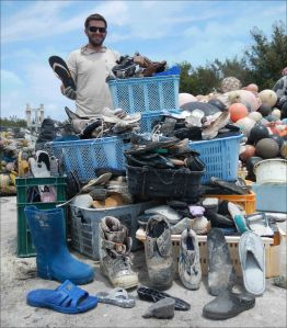 Edmund Coccagna on April 18 holds up a slipper and stands behind the other 885 slippers and rubber-soled shoes collected from the shorelines of Midway Atoll during this marine debris mission. NOAA photo by Kristen Kelly
