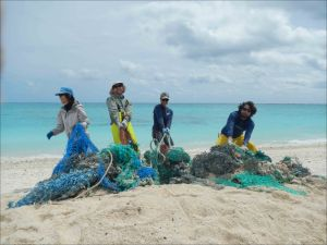 Tomoko Acoba, Russell Reardon, Kerrie Krosky, and Joao Garriques remove a large, buried derelict fishing net from the shoreline of Eastern Island on April 6. NOAA photo by Kristen Kelly