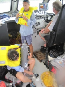 Kaylyn McCoy and Paula Ayotte process water samples, which later will be analyzed for dissolved inorganic carbon, while Captain Rob Crean keeps an eye on ocean conditions between dives at Atauro Island on June 6. NOAA photo by Andrew Gray