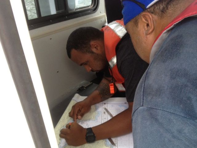 Samson Atoe, NPS, and Samuel Lili'u, Marine Patrol work together to plot fixes and navigate between waypoints in Pago Pago harbor.