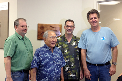 Sam Rauch, Frank Goto, Mike Tosatto and Sam Pooley in front of the recognition plaque  at the NOAA Fisheries Honolulu Service Center at Pier 38.