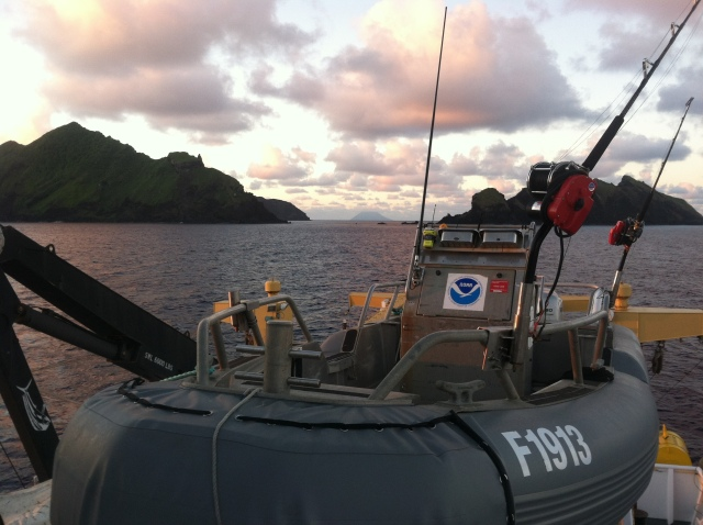 The PIFSC 19' Safe Boat sits in its cradle aboard the NOAA Ship Oscar Elton Sette, ready for its morning launch and operations at Maug. In the far background the island Asuncion sits off in the distance.