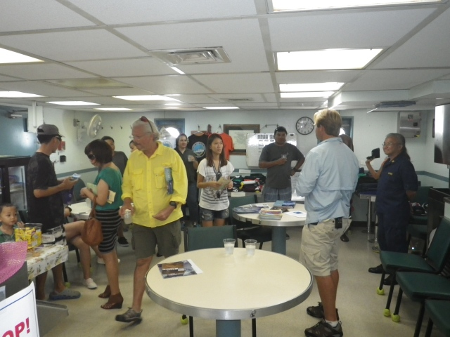 Open house visitors tour the galley and enjoy refreshments as Jamie Barlow explains the galley operations.