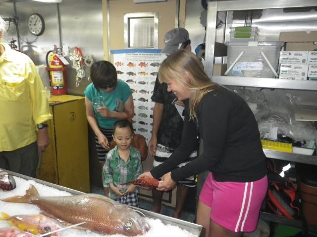 Fish Specialist, Megan Sundberg shows a grouper to a future marine biologist.