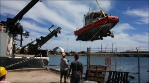 The R/V AHI, a PIFSC boat equipped with a multibeam mapping system, is loaded onto the R/V Kilo Moana, a vessel of the University of Hawai'i at Mānoa, in Honolulu on July 3 before the trip to French Polynesia. Note the cradle strapped to the AHI that enabled her to sit on the aft deck of the ship for the transit to Tahiti. NOAA photo by Kevin O'Brien
