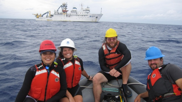 UOG students Taryn Mesa, Marylou Staman, Brad Wells and PIFSC Biotech Eric Mooney pose on a small boat with the Oscar Elton Sette in the background.