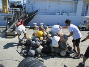 James Morioka organizes a cargo net full of plastic fishing floats.