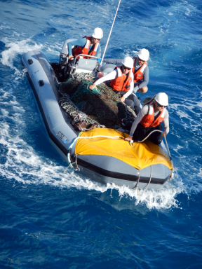 Marine debris boat team positioning themselves alongside the NOAA Ship Oscar Elton Sette following a productive day of survey and removal efforts at Maro Reef.