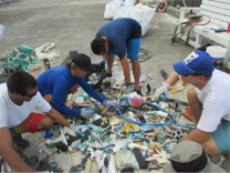 The marine debris team tediously sorts through piles of plastic that were collected following shoreline surveys on Eastern and Spit Island at Midway Atoll on October 7, 2014.
