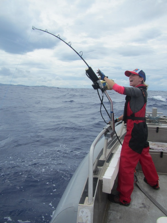 """Figure 3. Scientist excited about a fish on the line (if you listen carefully you can almost hear her yelling """"hanapa'a!""""). Notice the electric fishing reel."""
