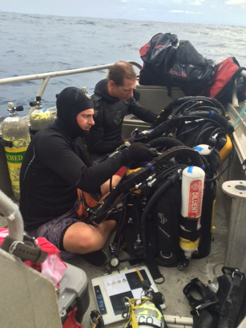 Figure 4: Andrew Gray and Tate Wester thoroughly examine and check their re-breather units prior to each dive. They are in the middle of their 16 action item checklist; demonstrating safe and best practices for closed circuit diving.