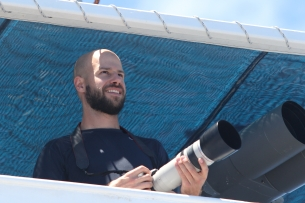 Duke PhD student Joe Fader takes photos from the flying bridge of the Sette during a cetacean sighting. Photo credit: NOAA Fisheries/Amanda Bradford