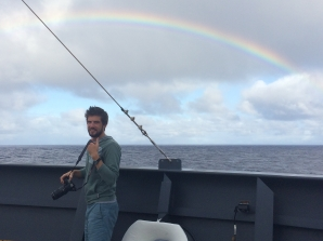 Duke PhD student Seth Sykora-Bodie watches a rainbow from the bow of the Lasker. Photo credit: NOAA Fisheries/Suzanne Yin